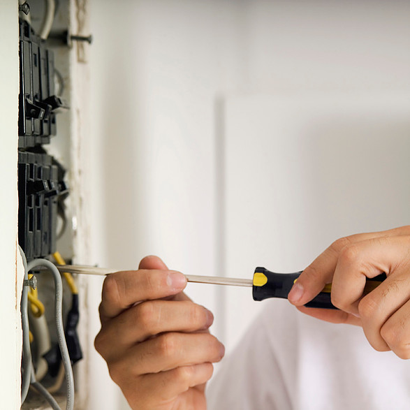Man using screwdriver on electric breaker box, close-up